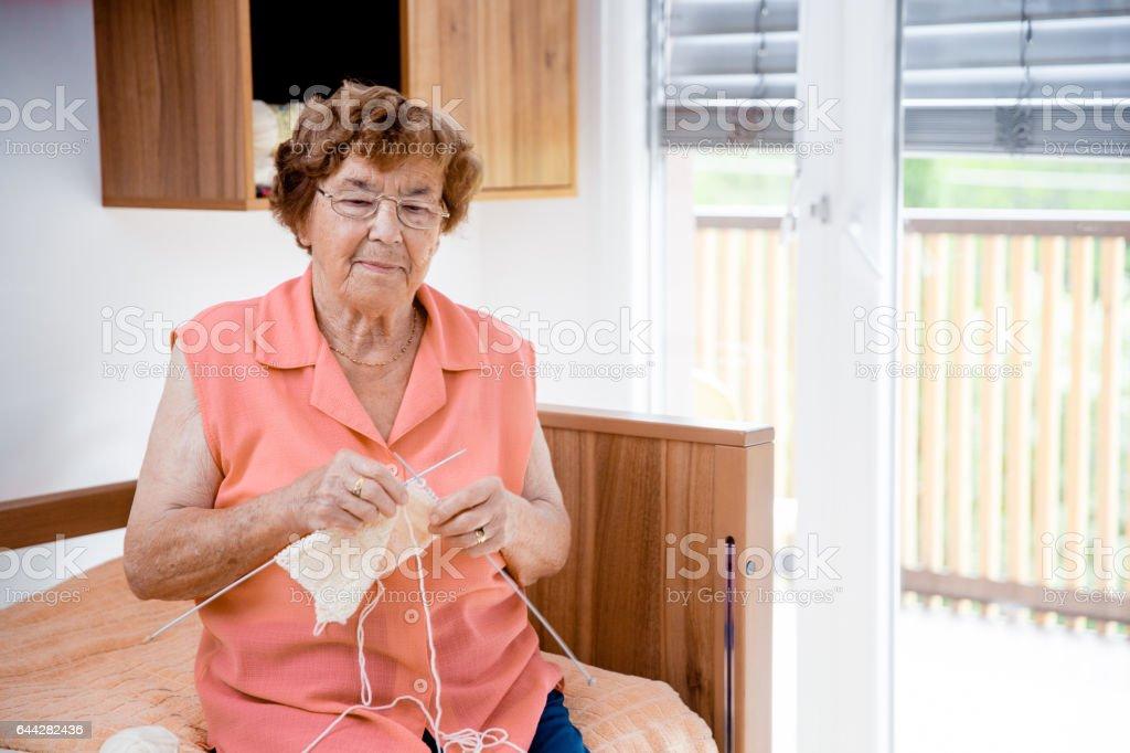 Senior Woman Doing Crochet In The Elderly Center stock photo