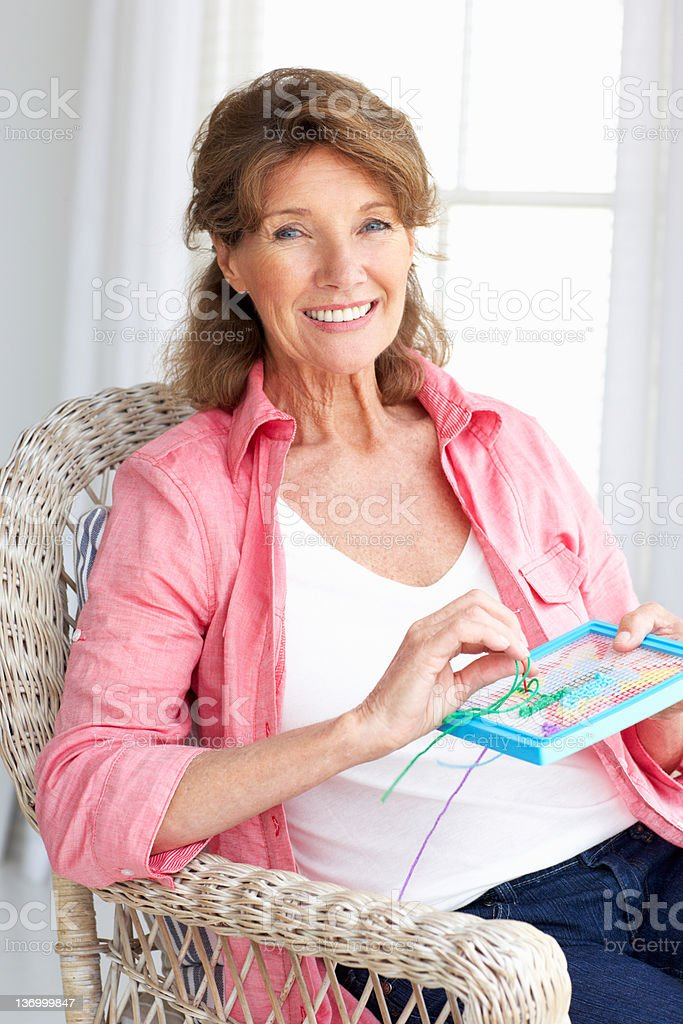 Senior woman doing cross stitch royalty-free stock photo