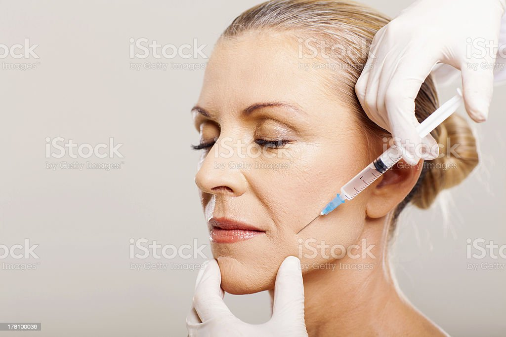 senior woman doing face lifting stock photo