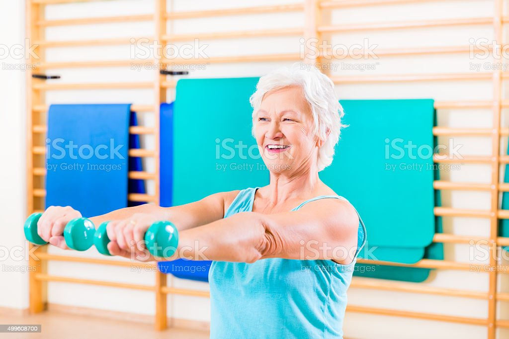 Senior woman doing fitness sport in gym stock photo