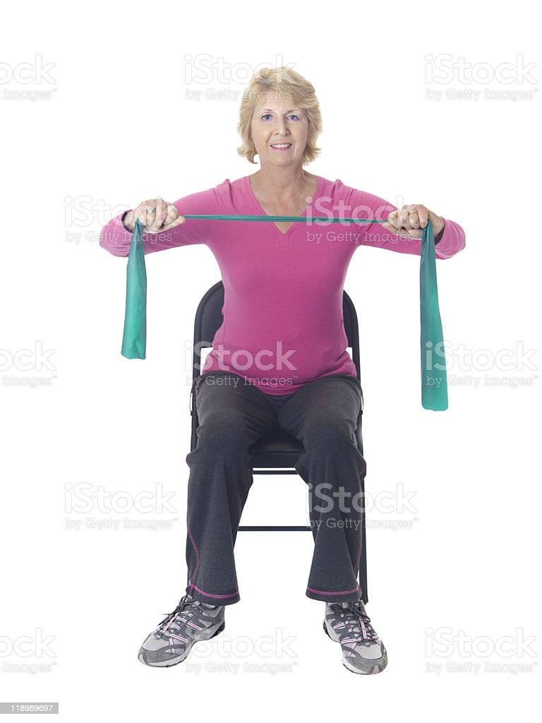 Senior woman doing strength exercise with resistance band in chair stock photo