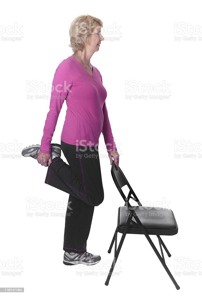Senior woman doing thigh stretch with chair royalty-free stock photo