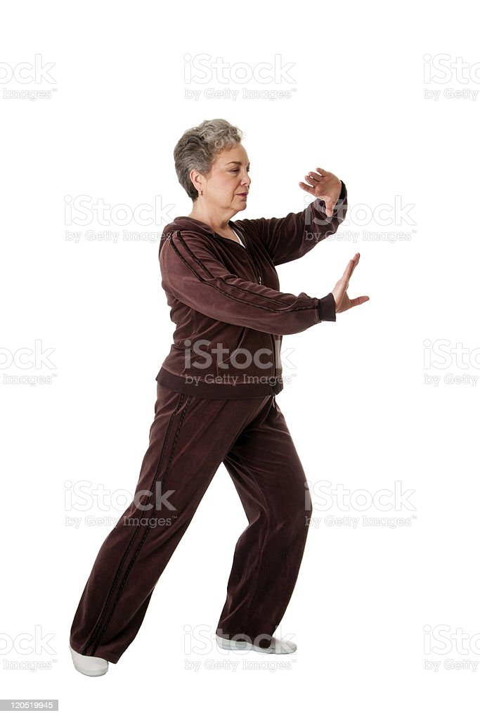 Senior woman dressed in brown doing Tai Chi Yoga exercise royalty-free stock photo