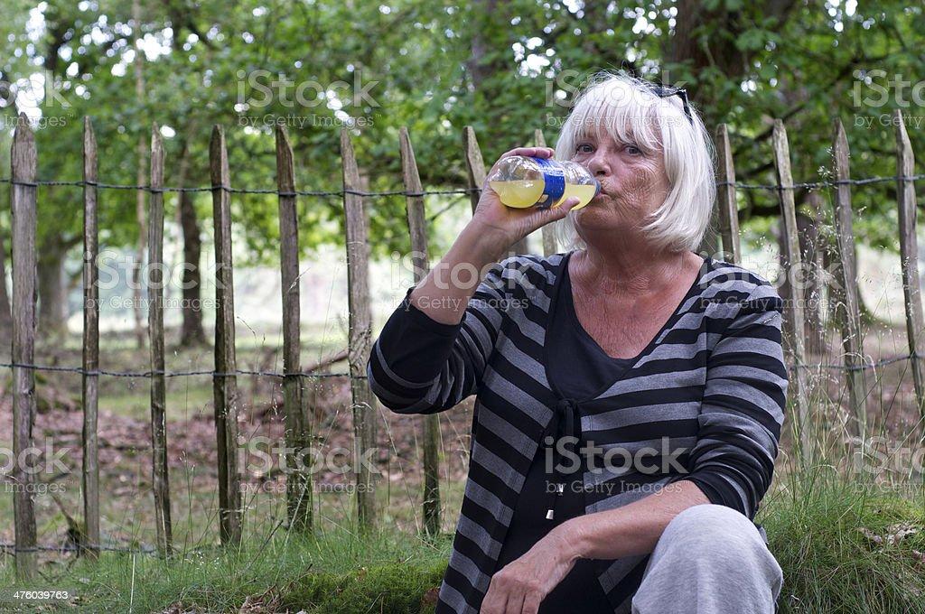 Senior woman drinking bottle of lemonade against fence royalty-free stock photo