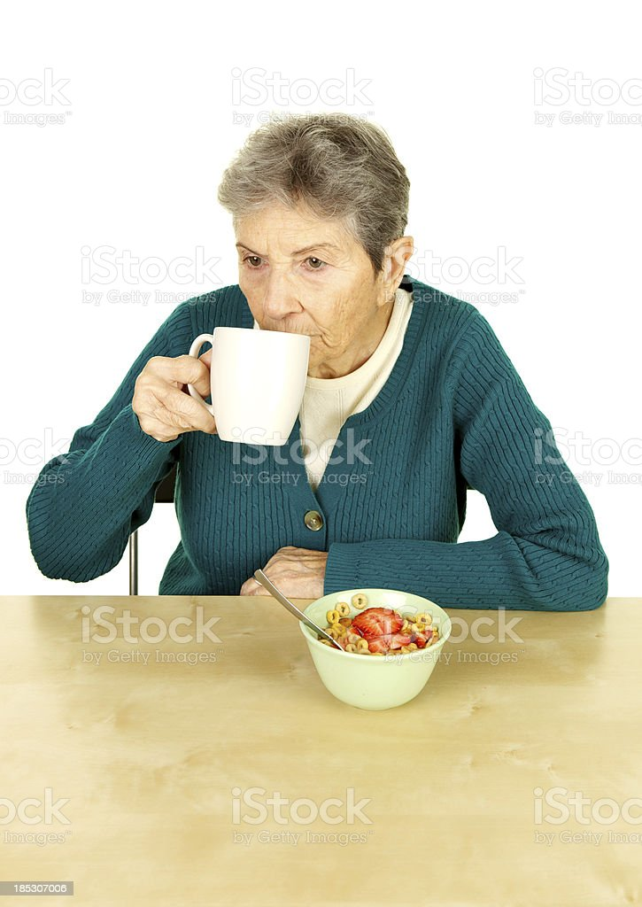 Senior Woman Drinking Coffee with Cereal Looking Sad stock photo