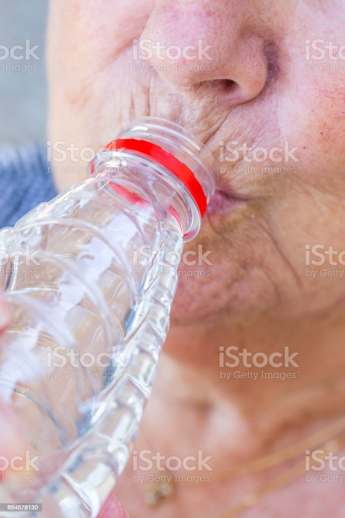 Senior Woman drinking fresh water from the bottle stock photo