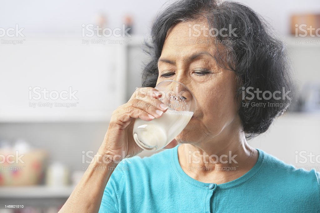 Senior woman drinking from a clear glass full of milk stock photo