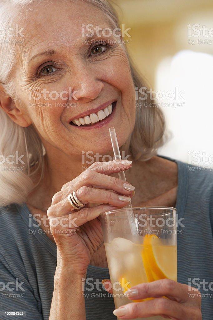 Senior woman drinking glass of lemonade royalty-free stock photo
