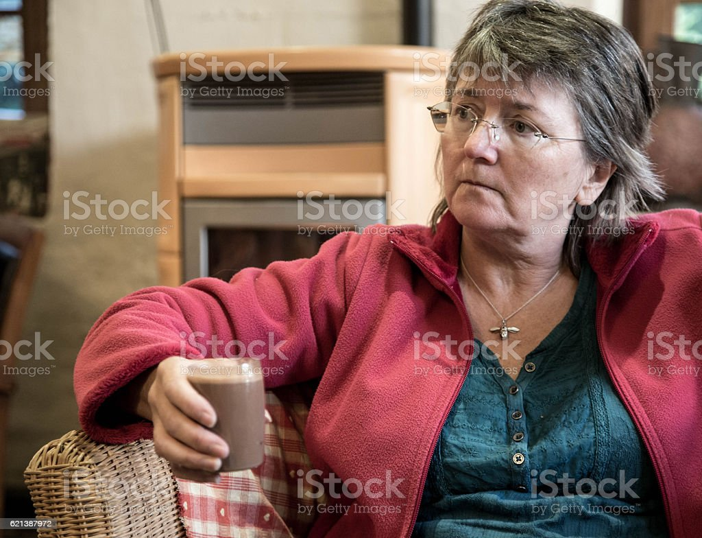 senior woman drinking hot chocolate in cafe stock photo