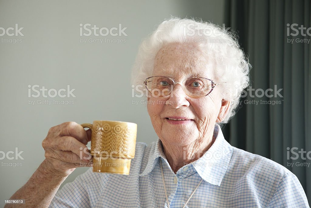 Senior woman drinking tea or coffee royalty-free stock photo