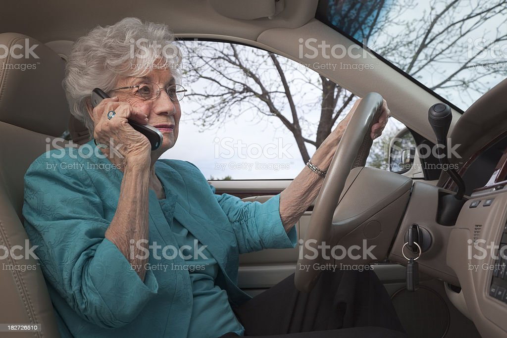 senior woman driving car talking on cell phone stock photo