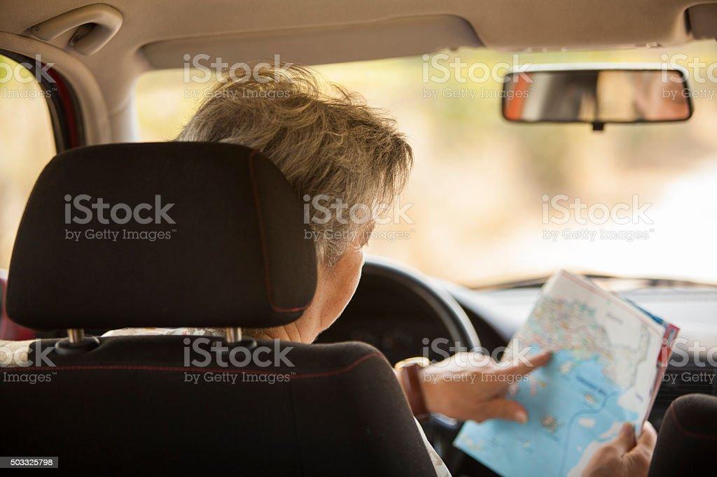 senior woman driving red car stock photo