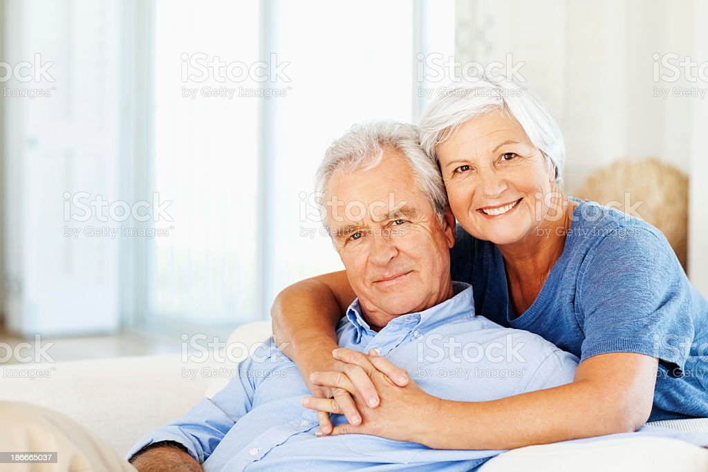 Senior Woman Embracing Man From Behind At Home stock photo