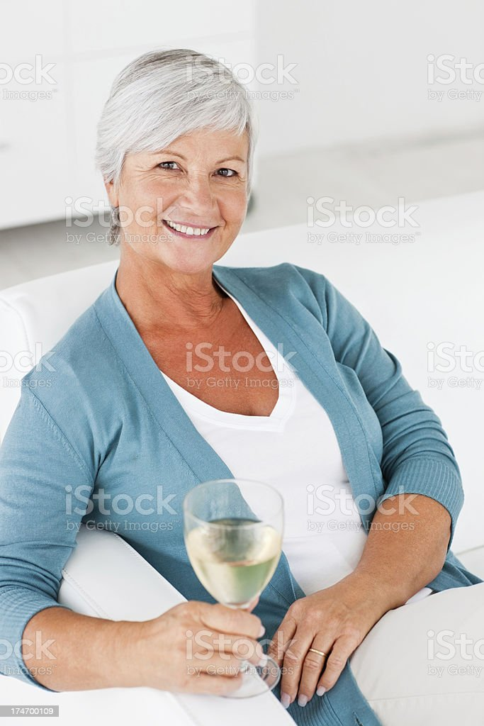 Senior woman enjoying a glass of champagne royalty-free stock photo