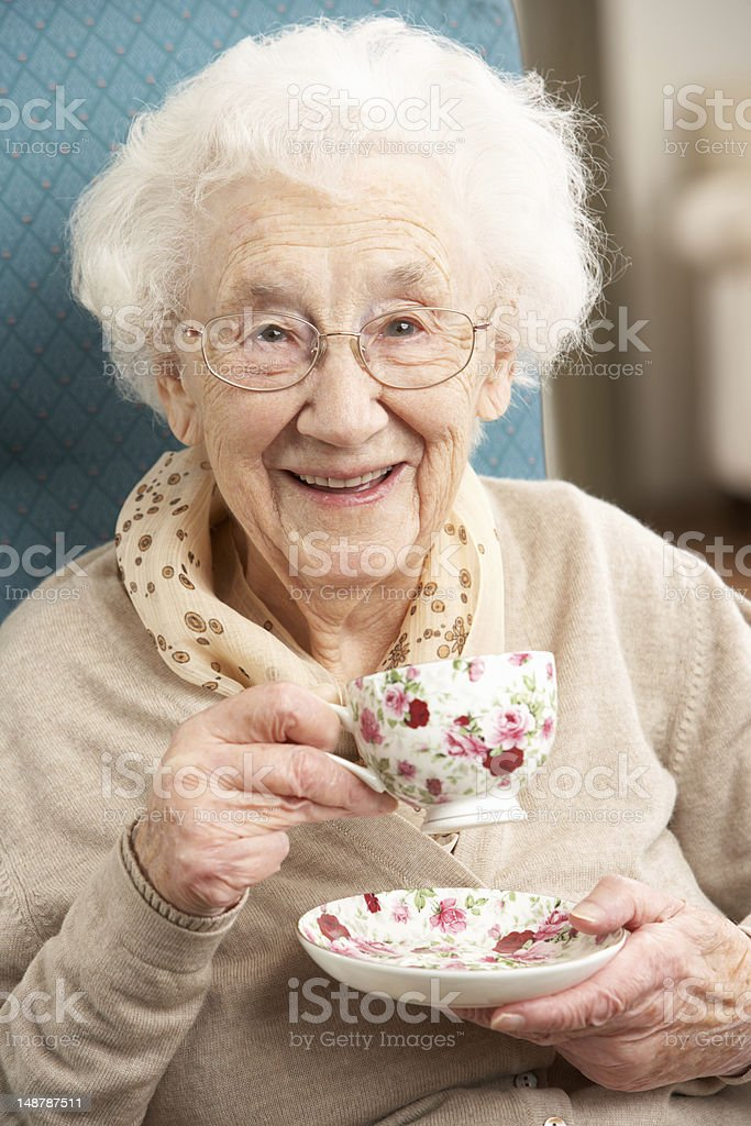 Senior Woman Enjoying Cup Of Tea At Home stock photo