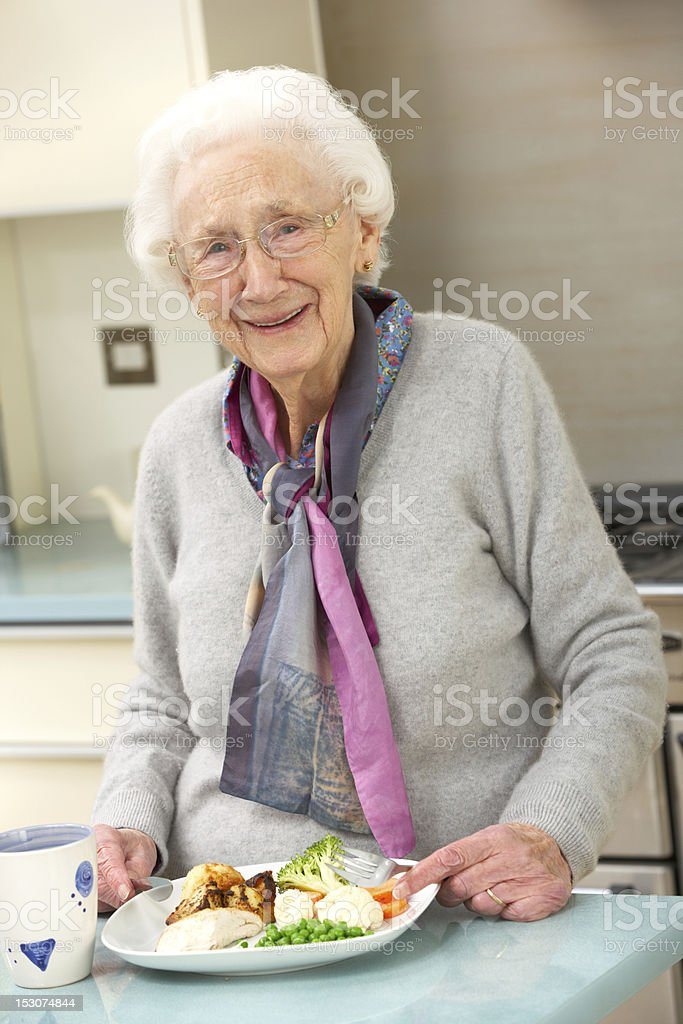 Senior woman enjoying meal in kitchen stock photo