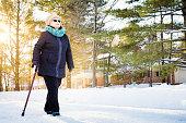 Senior woman enjoying walk with cane in Winter suburb