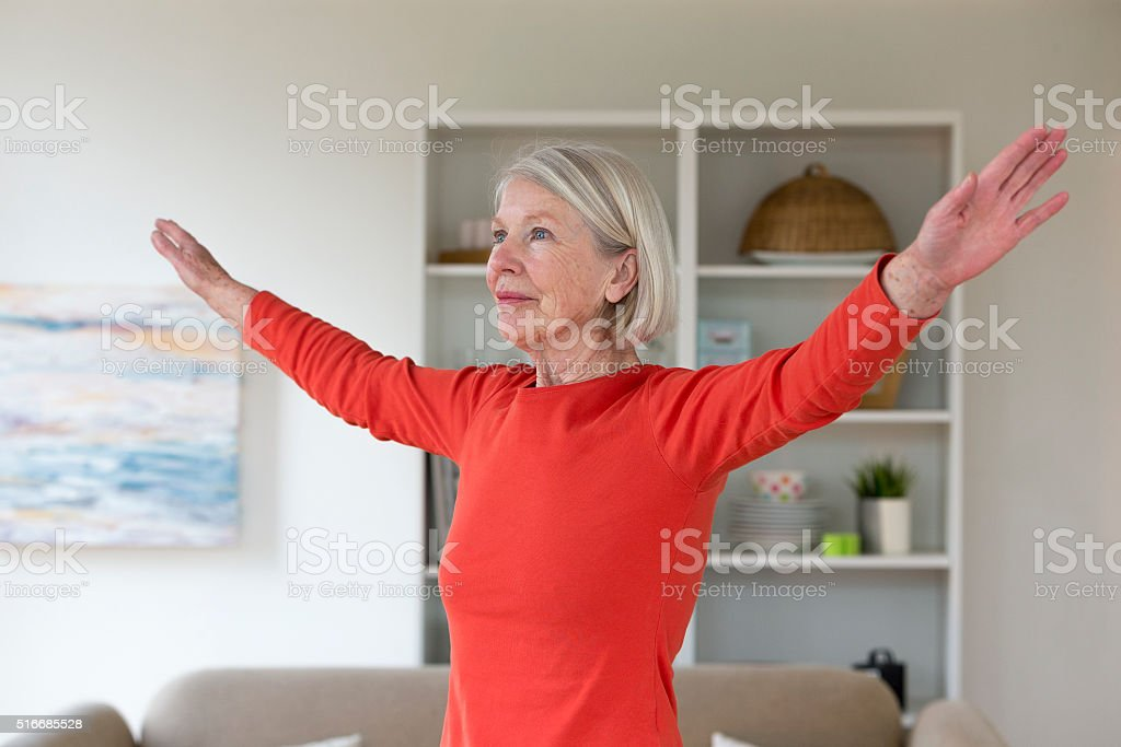 Senior woman exercising at home stock photo