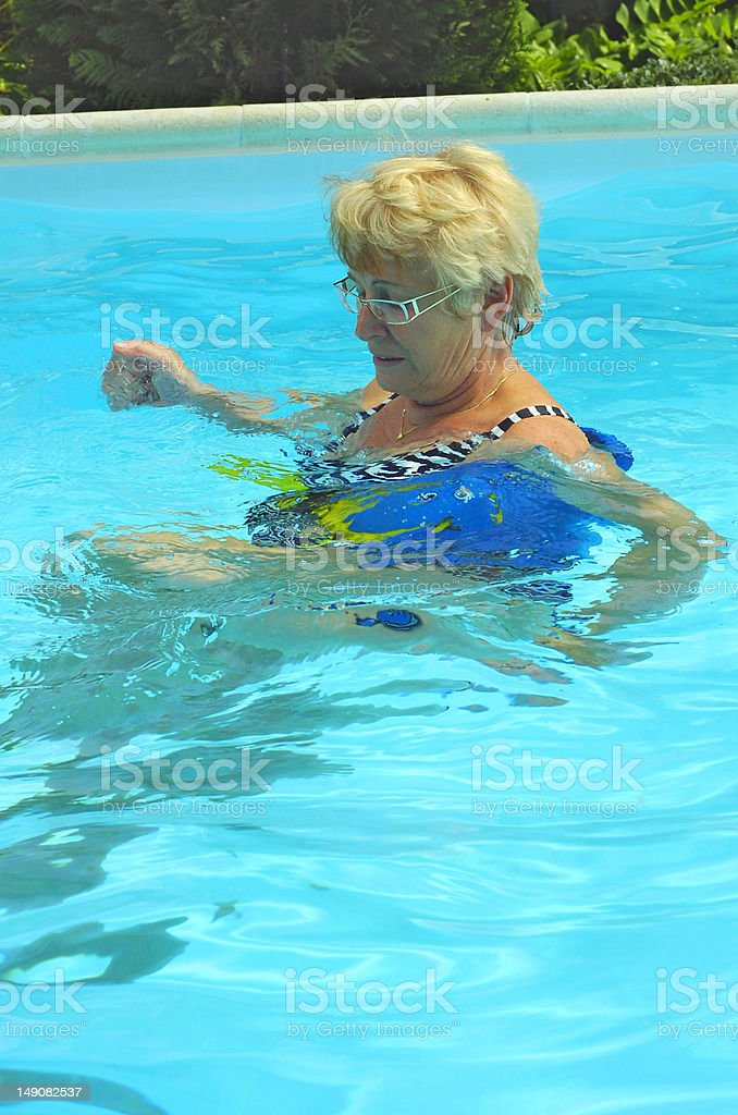 senior woman exercising in pool stock photo