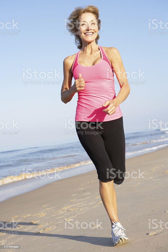 Senior Woman Exercising On Beach royalty-free stock photo