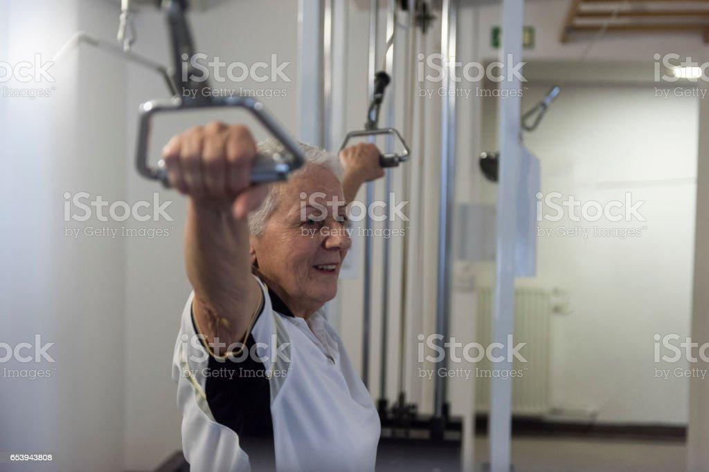 Senior woman exercising on machine at gym stock photo