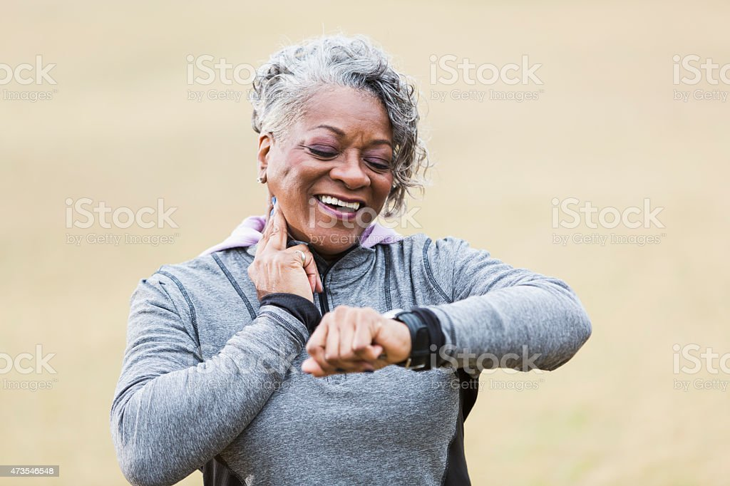 Senior woman exercising, taking pulse stock photo