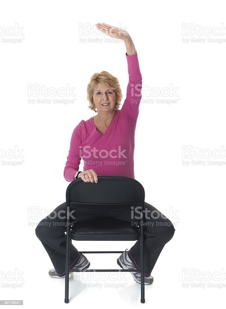 Senior woman exercising while seated stock photo