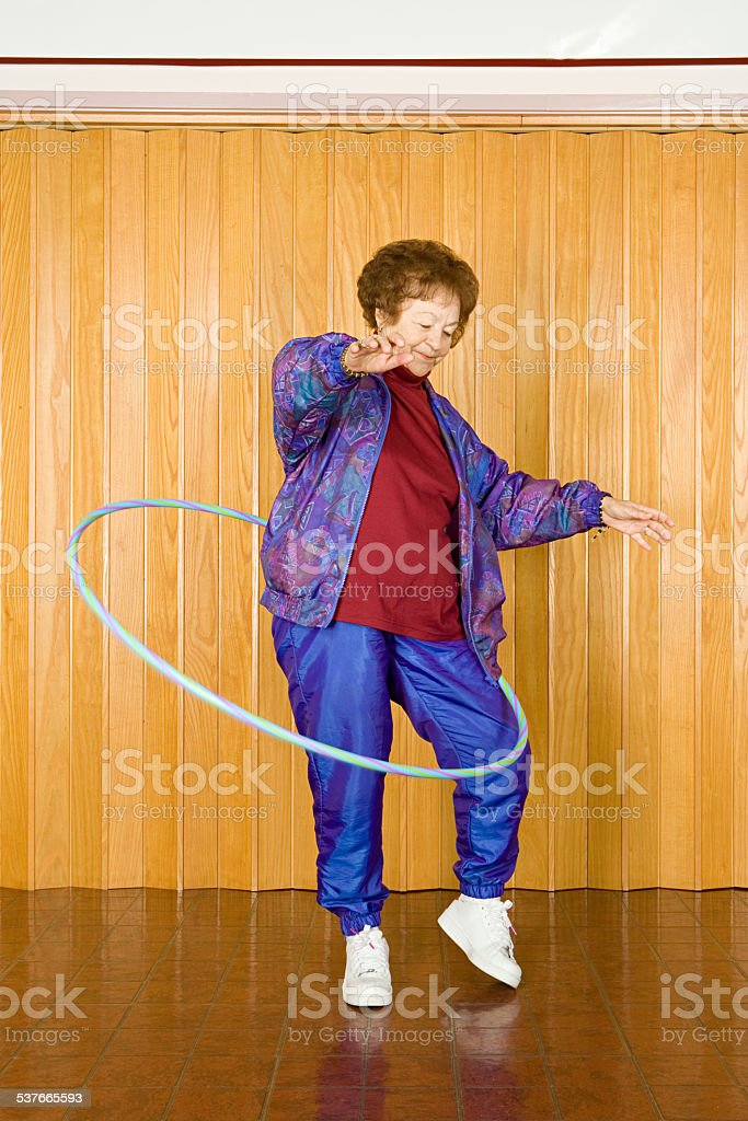 Senior woman exercising with a hula hoop stock photo