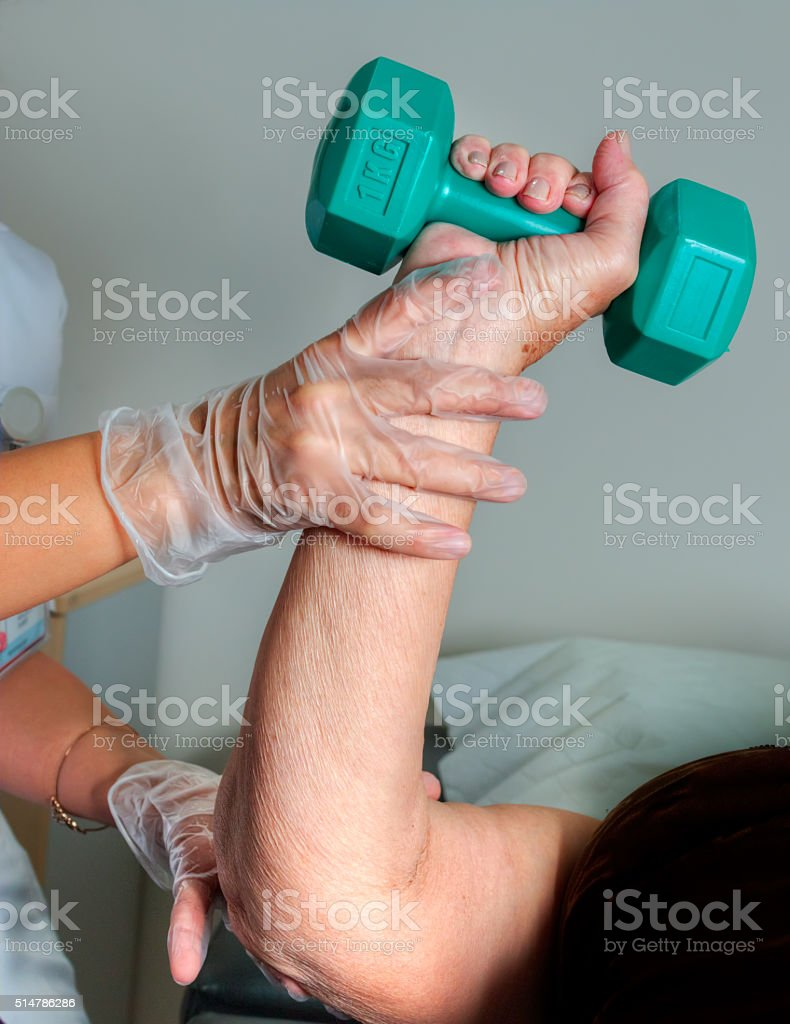Senior Woman exercising with dumbbells in rehabilitation clinic stock photo