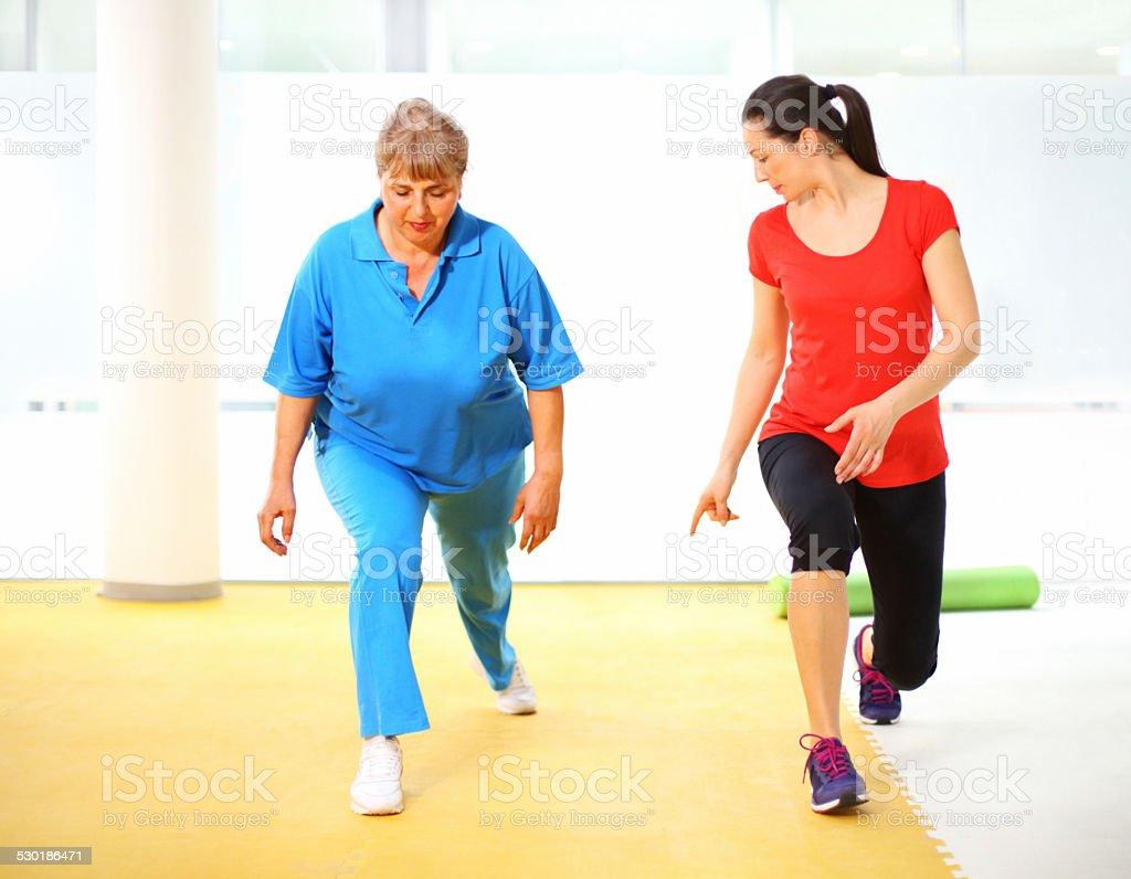 Senior woman exercising with instructor. stock photo