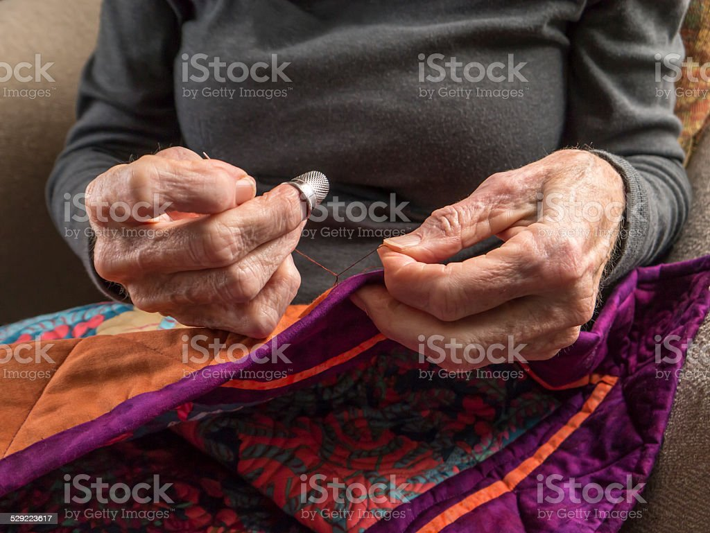 Senior Woman Expertly Stitches the Binding Onto Her Quilt stock photo