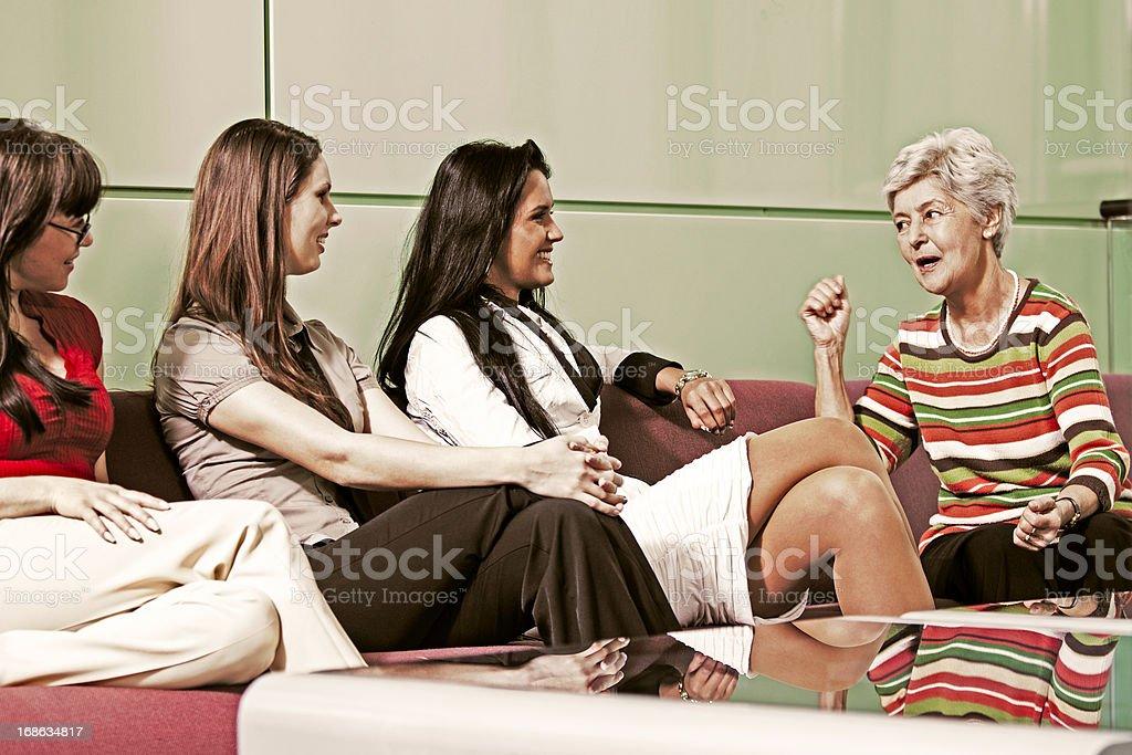 Senior woman explaining something to group of young women royalty-free stock photo