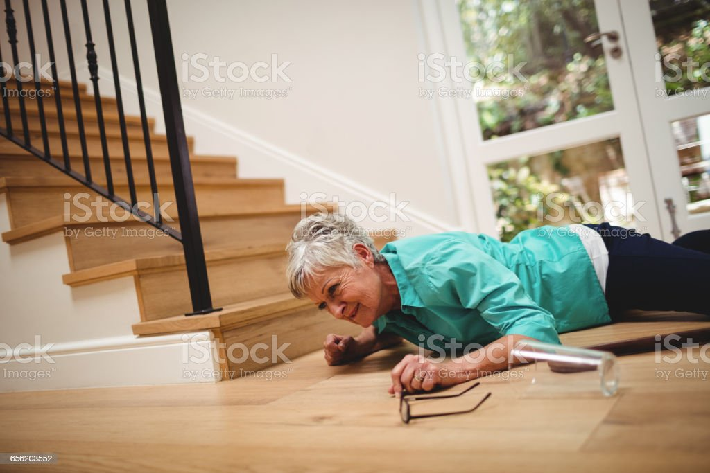 Senior woman fallen down from stairs stock photo