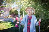 Senior woman gardening, holding a pitchfork and a rake