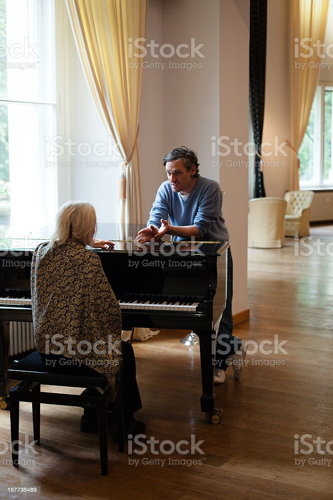 senior woman gets a music lesson at a grand piano stock photo