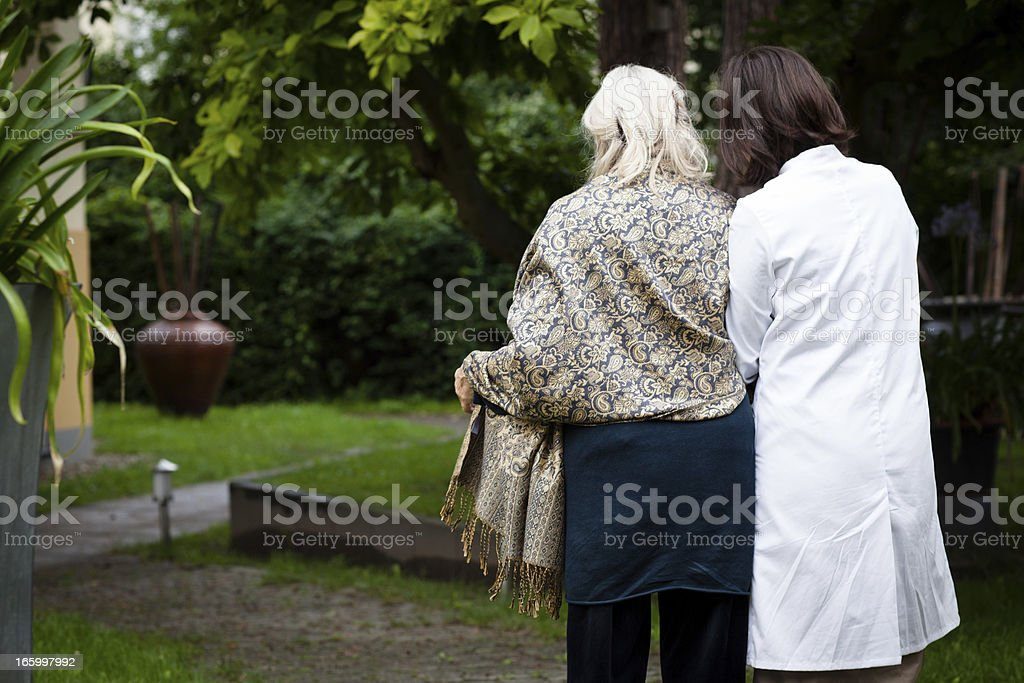 senior woman gets help from nurse for a walk royalty-free stock photo