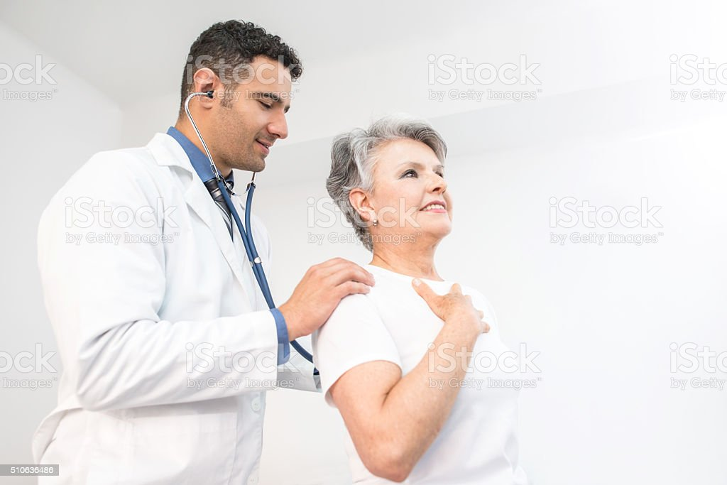 Senior woman getting a medical exam at the doctor stock photo