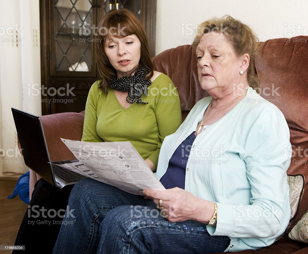 Senior woman getting assistance paying bills online royalty-free stock photo