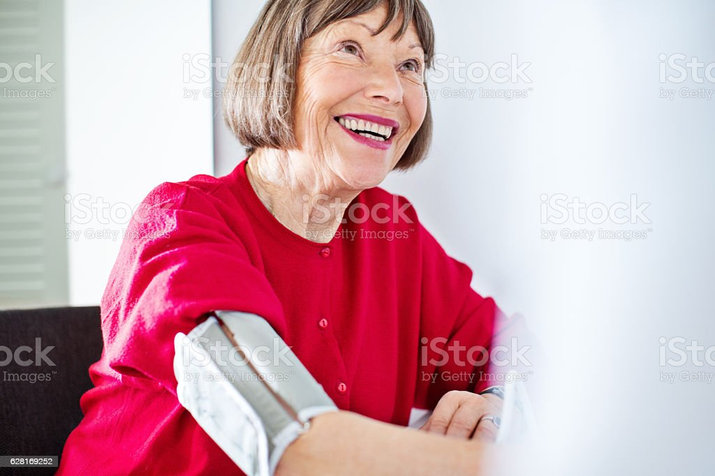 Senior woman getting blood pressure checked stock photo