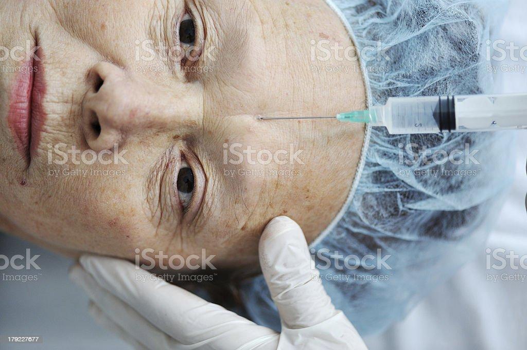 Senior woman getting botox injection at hospital royalty-free stock photo