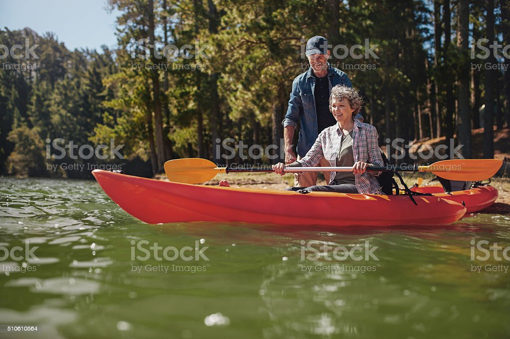 Senior woman getting kayaking lessons from a man stock photo