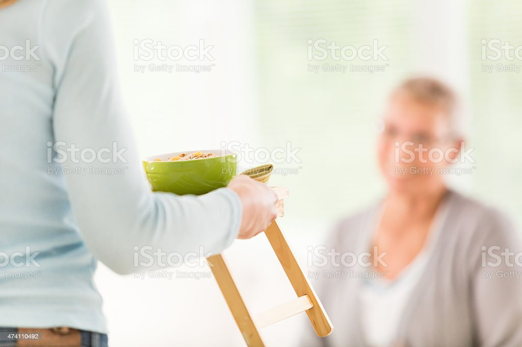 Senior woman getting meal served in bed stock photo