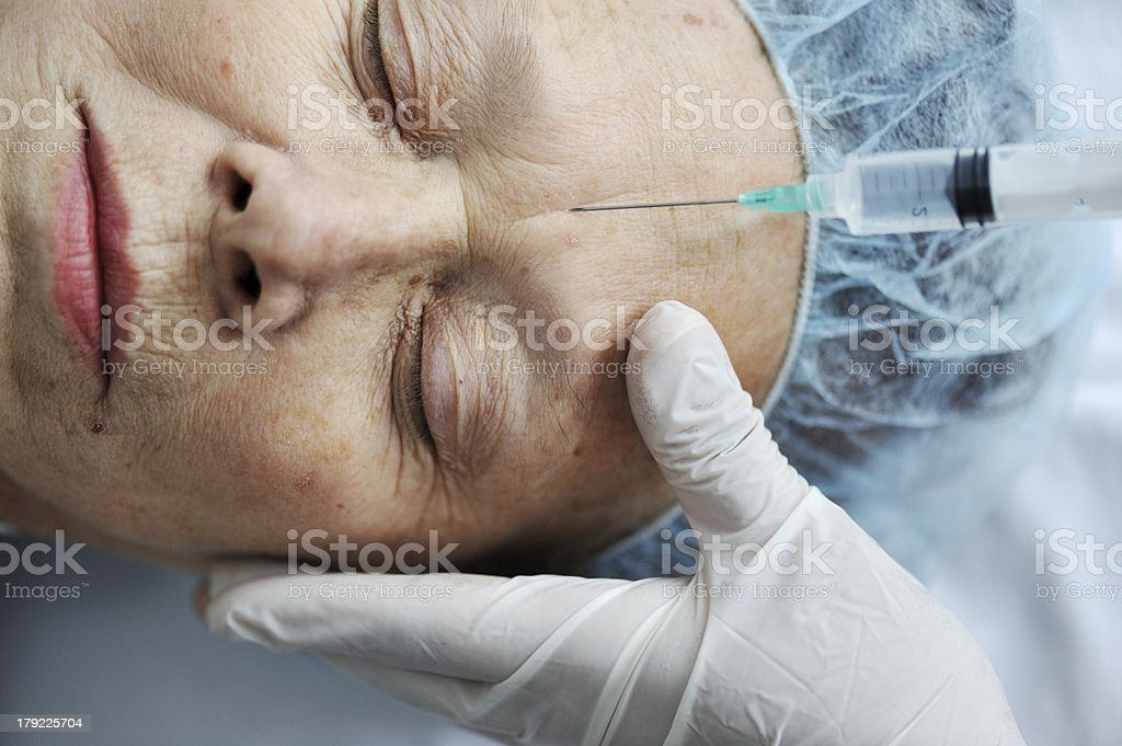 Senior woman getting on face injection at hospital royalty-free stock photo