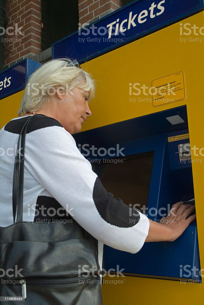 Senior woman getting traintickets with creditcard royalty-free stock photo