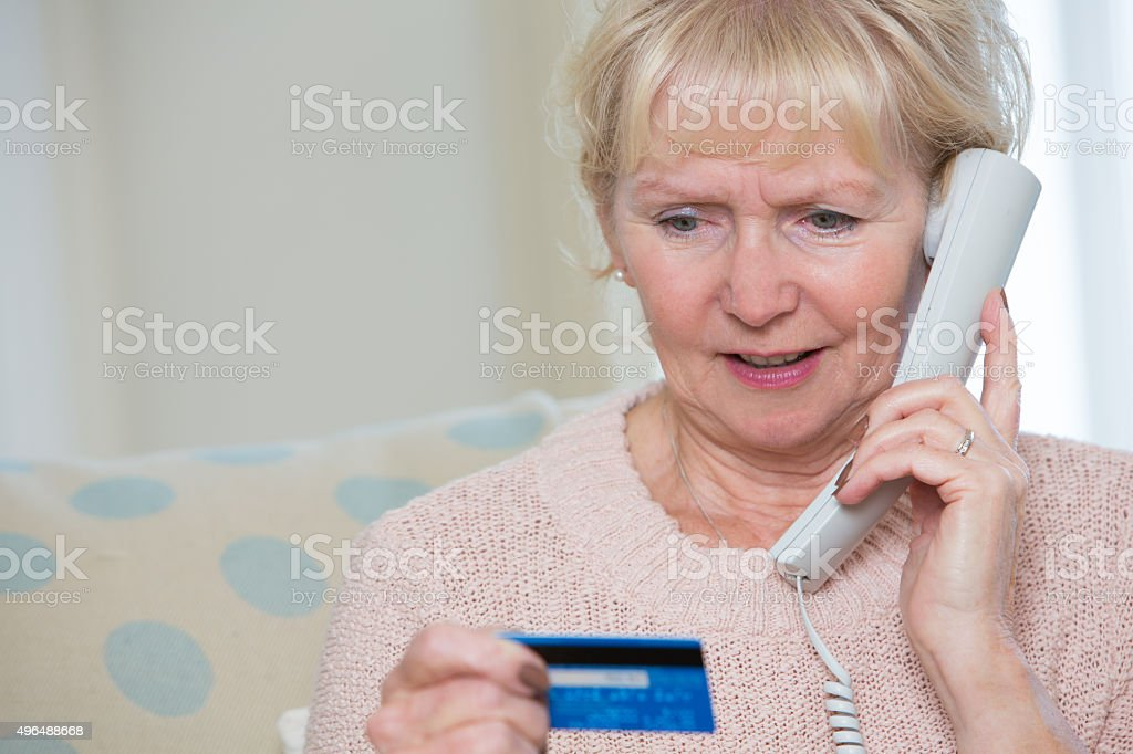 Senior Woman Giving Credit Card Details On The Phone stock photo