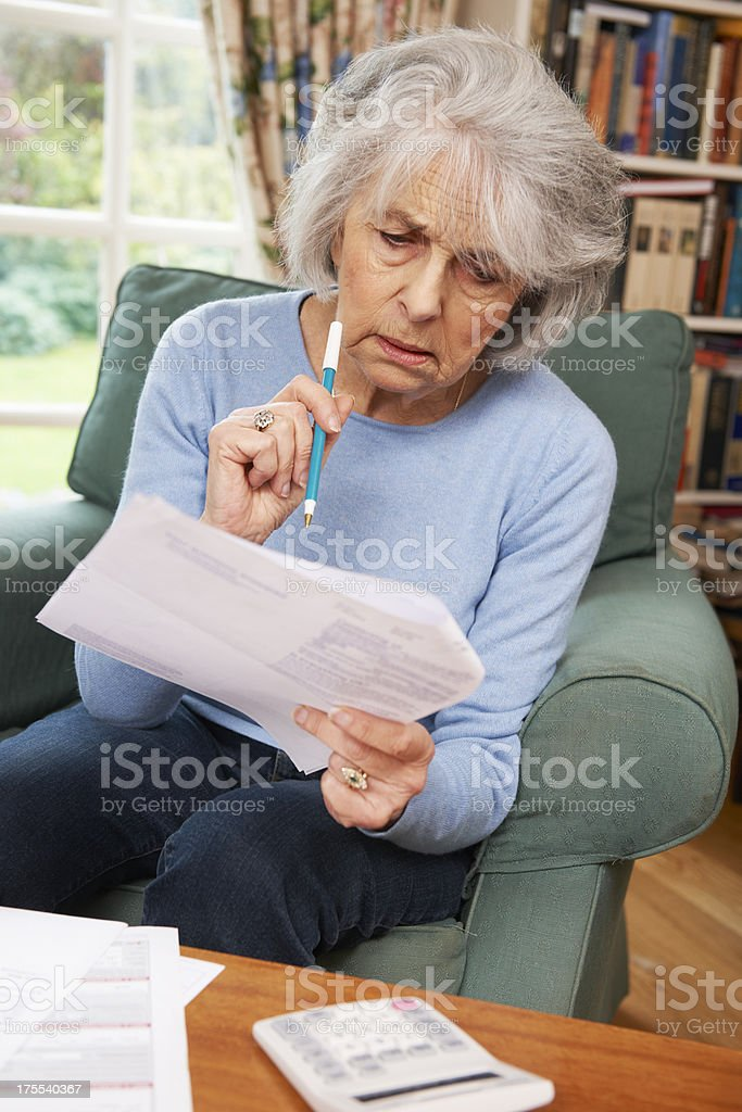 Senior Woman Going Through Bills And Looking Worried royalty-free stock photo