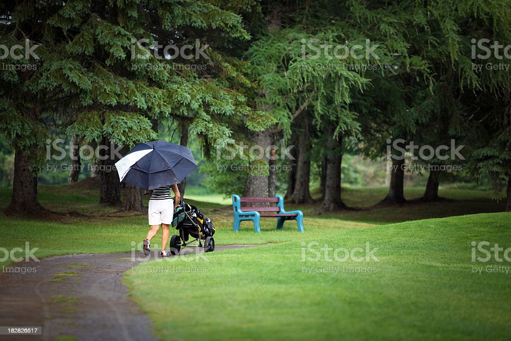 Senior Woman Golf Player Walking with Trolley and Umbrella royalty-free stock photo