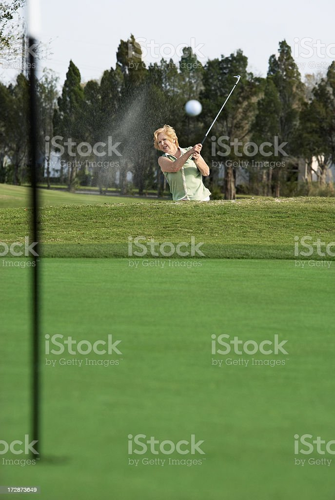 senior woman golfer in bunker royalty-free stock photo