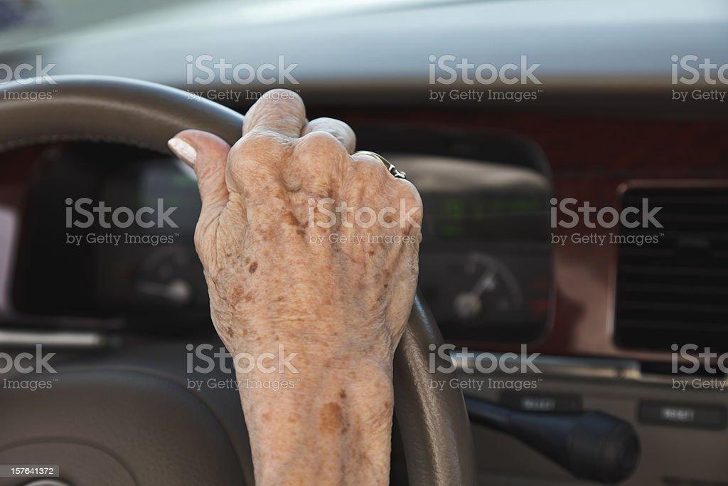 senior woman hand on steering wheel stock photo