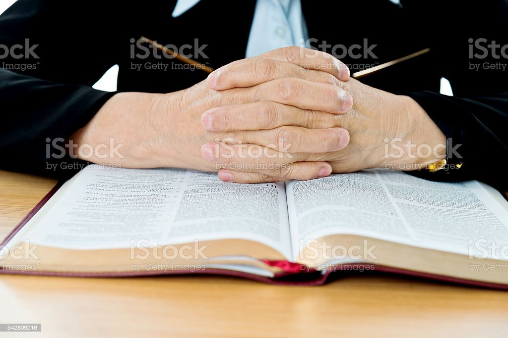 Senior woman hands clasped on bible book stock photo